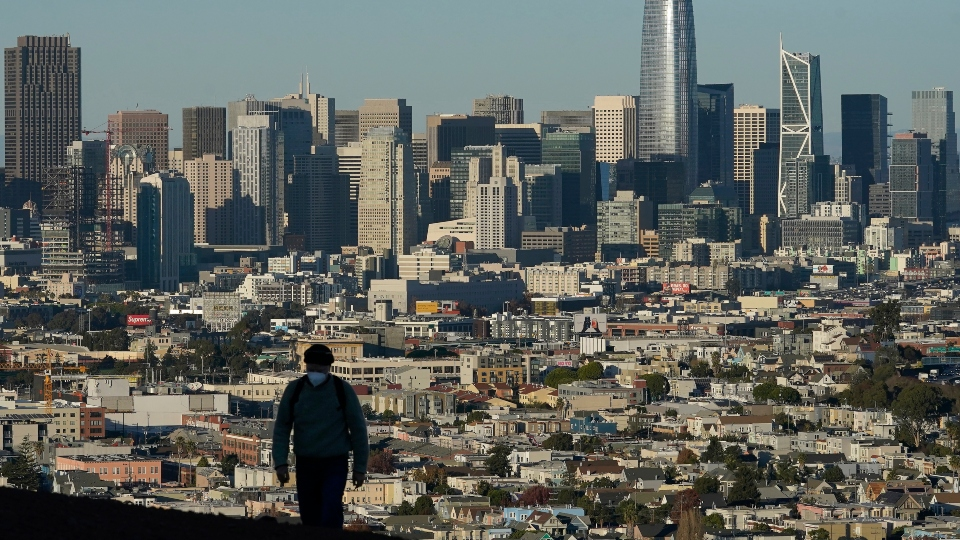 In this Dec. 7, 2020, file photo, a person wearing a protective mask walks in front of the skyline on Bernal Heights Hill during the coronavirus pandemic in San Francisco.