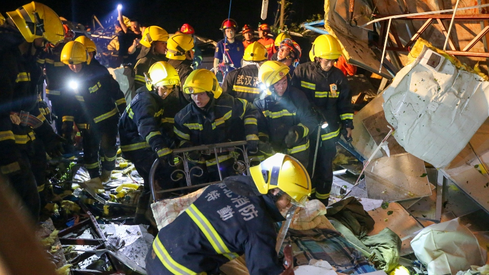 In this photo released by China's Xinhua News Agency, emergency personnel search through the wreckage of buildings destroyed by a reported tornado in Wuhan in central China's Hubei Province, early Saturday, May 15, 2021.