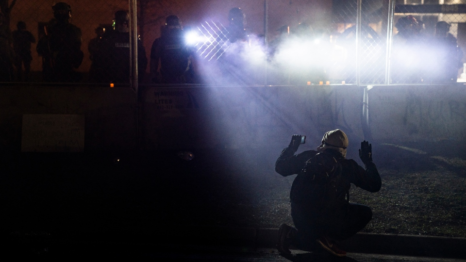 In this April 14, 2021, file photo, police shine lights on a demonstrator with raised hands during a protest outside the Brooklyn Center Police Department on in Brooklyn Center, Minn., over the fatal shooting of Daunte Wright.