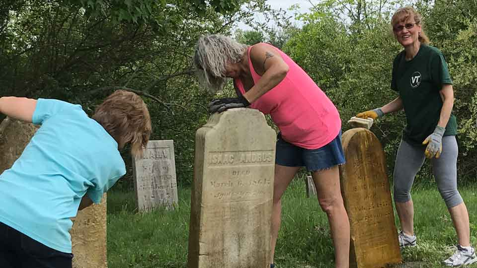 Members of the Vienna Historical Society work to restore and clean tombstones in Doud Cemetery on May 22, 2021. Photo Credit: Vienna Historical Society