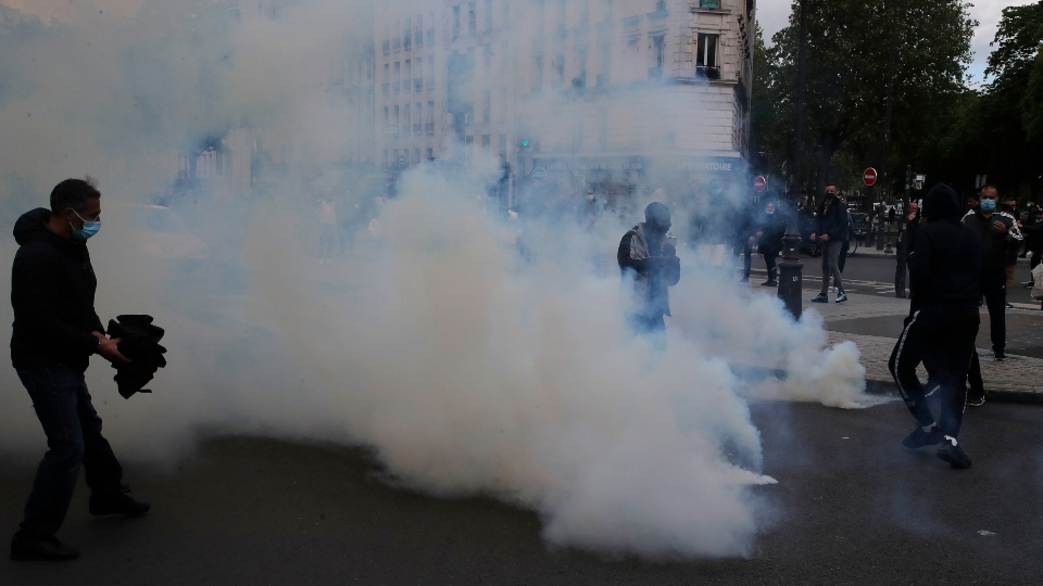 Demonstrators walk through tear gas grenades fired by police forces during a banned protest in support of Palestinians in the Gaza Strip, Saturday, May, 15, 2021 in Paris.