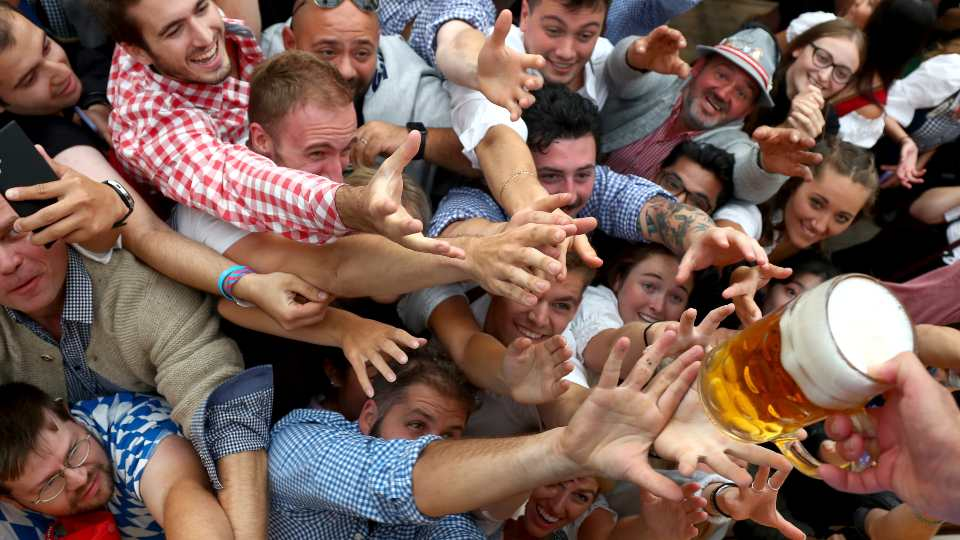 In this file photo dated Saturday, Sept. 21, 2019, people reach out for a glass of beer during the opening of the 186th 'Oktoberfest' beer festival in Munich, Germany. Bavarian officials have announced Monday May 3, 2021, they have canceled Oktoberfest festivities for the second year in a row due to concerns over the spread of the coronavirus global pandemic.