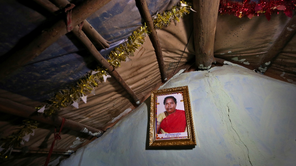 A portrait of Padmavathi, who died of COVID-19, hangs on the wall of her family hut made from bamboo and plastic sheeting in a slum in Bengaluru, India, Thursday, May 20, 2021. Padmavathi collected hair, taking it from women's combs and hairbrushes to later be used for wigs. She earned about $50 a month.