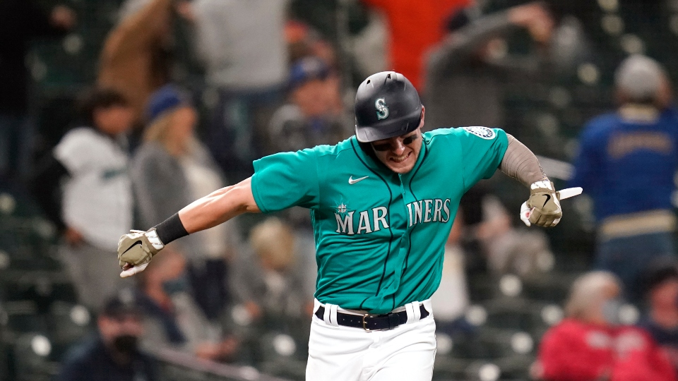 Seattle Mariners' Jarred Kelenic reacts to the home run of Mitch Haniger as he heads in to score against the Cleveland Indians during the seventh inning of a baseball game Friday, May 14, 2021, in Seattle.