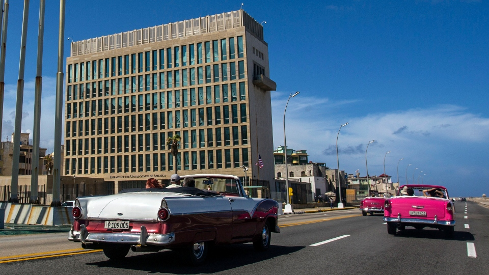 In this Oct. 3, 2017, file photo, tourists ride classic convertible cars on the Malecon beside the United States Embassy in Havana, Cuba.