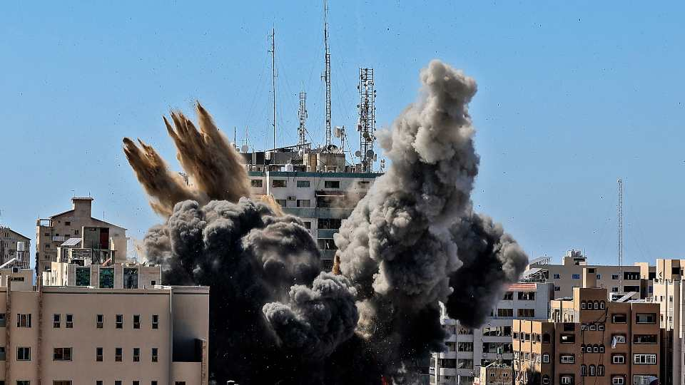 In this Saturday, May 15, 2021, file photo, an air bomb hits the building housing various international media, including The Associated Press, in Gaza City. Israel's defense minister has distanced himself from comments made by his military chief after Israel bombed the Gaza Strip high-rise housing an Associated Press office and other news outlets.