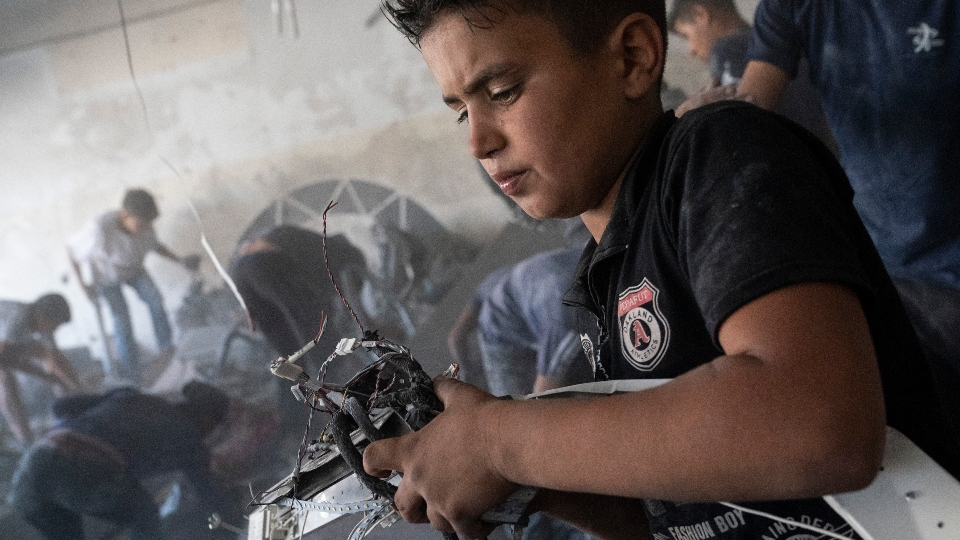 Children scavenge debris from a building severely damaged by an air-strike prior to a cease-fire reached after an 11-day war between Gaza's Hamas rulers and Israel.