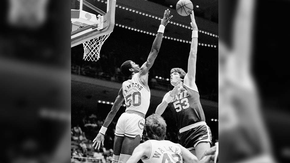 In this Nov. 11, 1983, file photo, Utah Jazz center Mark Eaton , right, puts a hook shot up and over the outstretched hand of Houston Rocket center Ralph Sampson during the first period of an NBA basketball game at the Summit in Houston. Eaton, the 7-foot-4 shot-blocking king who twice was the NBA's defensive player of the year during his career with the Utah Jazz, has died, the team said Saturday, May 29, 2021. He was 64.