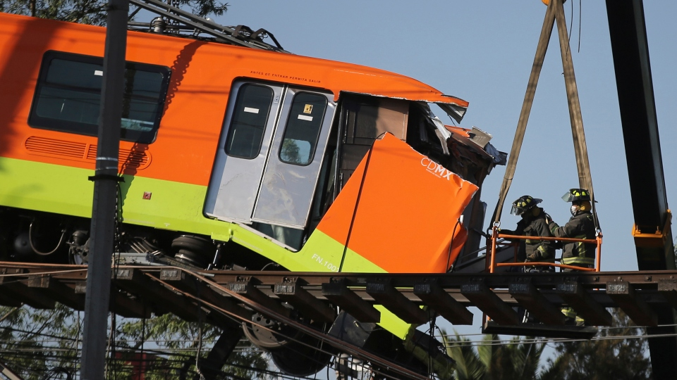 Firefighters work to lower to the ground a subway car dangling from a collapsed elevated section of the metro, in Mexico City, Tuesday, May 4, 2021.