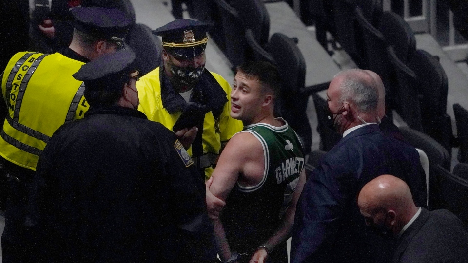 A fan is handcuffed and escorted out of TD Garden by police after allegedly throwing a water bottle at Brooklyn Nets' Kyrie Irving as Irving left the court after Game 4 of an NBA basketball first-round playoff series, Sunday, May 30, 2021, in Boston.