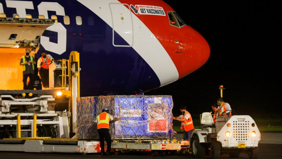 In this photo provided by El Salvador's presidential press office, airport workers unload a container of Chinese-made Sinovac COVID-19 vaccines from The New England Patriots team plane at the airport in San Salvador, El Salvador, late Tuesday, May 18, 2021.
