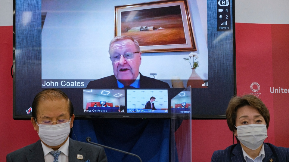 In this May 21, 2021, file photo, CEO of the Tokyo 2020 Toshiro Muto, left, and President of the Tokyo 2020 Seiko Hashimoto, right, listen to IOC Vice President John Coates, (on screen), delivering a speech during the Tokyo 2020 IOC Coordination Commission press conference in Tokyo.