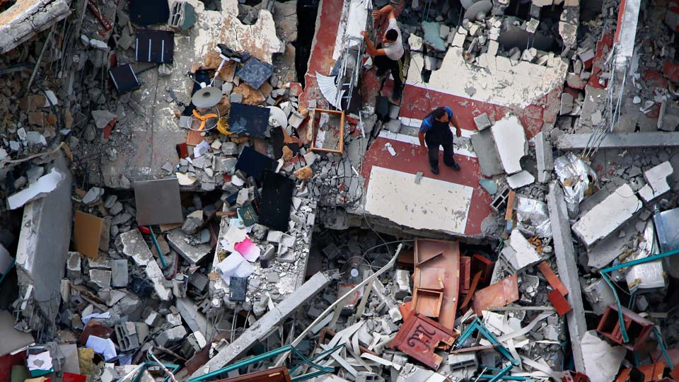 Palestinians inspect the destroyed building housing the offices of The Associated Press and other media, after it was hit last week by Israeli airstrike, in Gaza City, Friday, May 21, 2021. A cease-fire took effect early Friday after 11 days of heavy fighting between Israel and Gaza's militant Hamas rulers that was ignited by protests and clashes in Jerusalem. (AP Photo/Hatem Moussa)