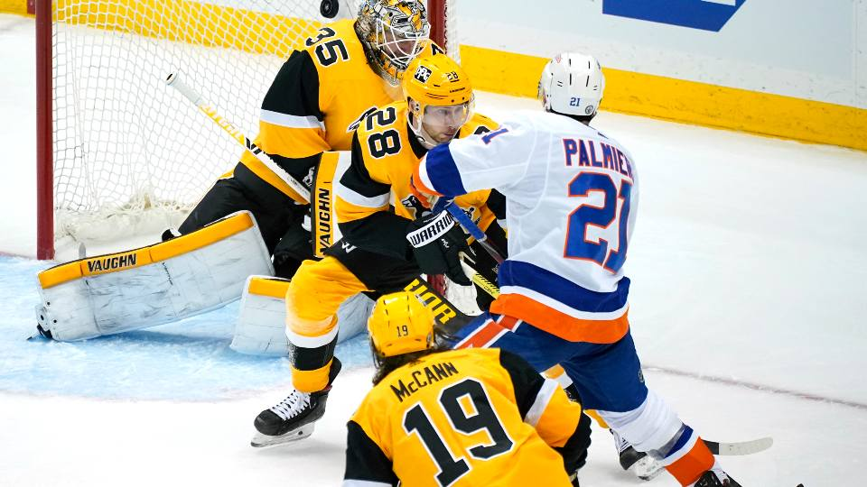 New York Islanders' Kyle Palmieri (21) puts a shot over Pittsburgh Penguins goaltender Tristan Jarry (35) with Marcus Pettersson (28) defending for the game-winning goal in overtime in Game 1 of an NHL hockey Stanley Cup first-round playoff series in Pittsburgh, Sunday, May 16, 2021. The Islanders won 4-3.