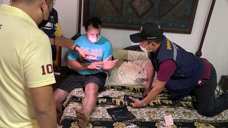 In this Thursday, May 6, 2021, photo released by the Thai Provincial Police Region 5, police arrest and interrogate American citizen Jason Matthew Balzer, center, in Chiang Mai province northern Thailand before charging him for intentionally murdering his pregnant wife in Nan province.