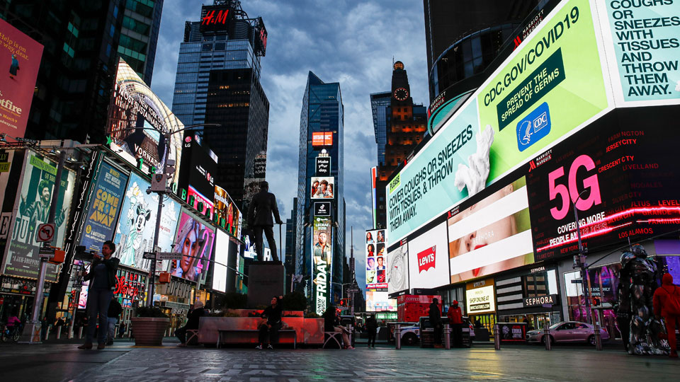 A screen displaying messages about COVID-19 light up a sparsely populated Times Square in New York on March 20, 2020