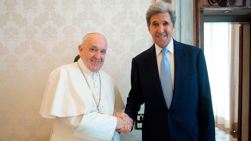 Pope Francis and John Kerry, right, shake hands as they pose for a photo at the Vatican, Saturday, May 15, 2021.