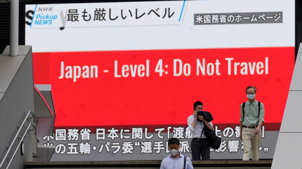People wearing masks to help protect against the spread of the coronavirus walk in front of a screen showing the news on U.S. warning against visits to Japan Tuesday, May 25, 2021, in Tokyo.
