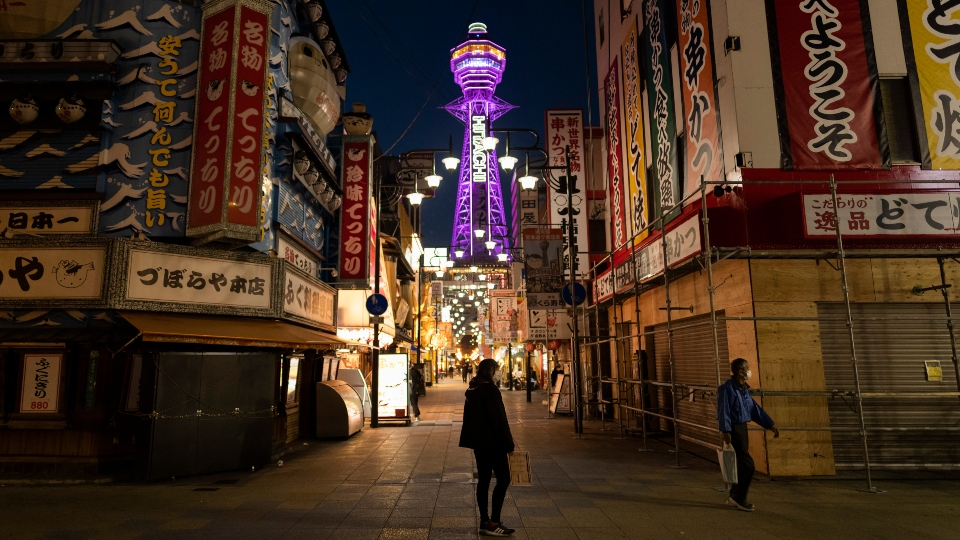 In this April 19, 2021, file photo, a restaurant staff member, center, stands in the middle of a street to promote her establishment at one of the famous commercial districts in Osaka, western Japan