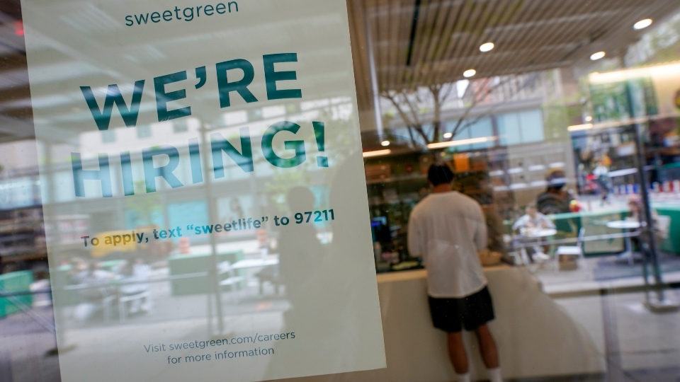 A signs announcing they are hiring hangs in the window of a restaurant in the Greenwich Village neighborhood of Manhattan in New York, Tuesday, May 4, 2021.