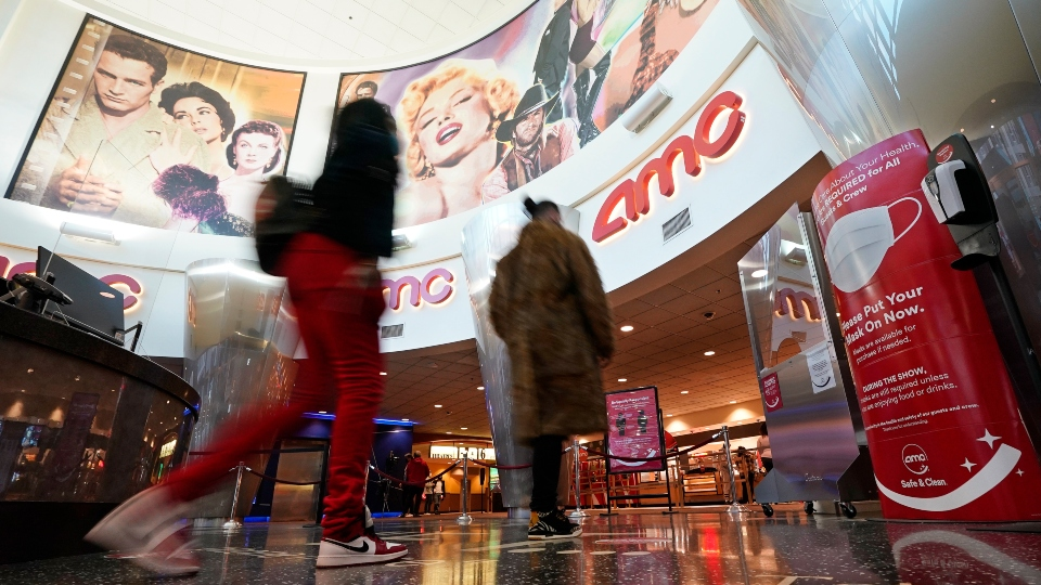 In this March 15, 2021, file photo movie patrons arrive to see a film at the AMC 16 theater in Burbank, Calif.