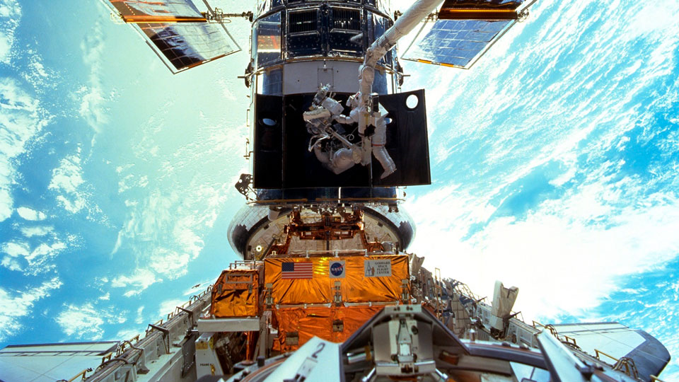 Astronauts Steven L. Smith and John M. Grunsfeld are photographed during an extravehicular activity (EVA) during the December 1999 Hubble servicing mission of STS-103, flown by Discovery