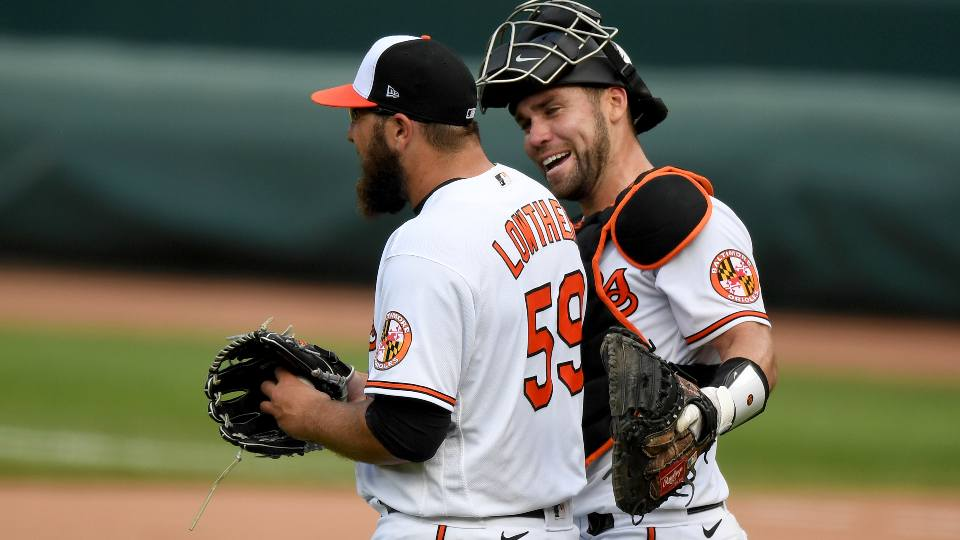 Baltimore Orioles catcher Austin Wynns celebrates with Zac Lowther (59) after defeating the Cleveland Indians in a baseball game, Sunday, June 6, 2021, in Baltimore.