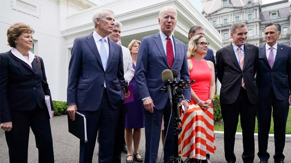 President Joe Biden, with a bipartisan group of senators, speaks Thursday June 24, 2021, outside the White House in Washington. Biden invited members of the group of 21 Republican and Democratic senators to discuss the infrastructure plan. From left are, Sen. Jeanne Shaheen, D-N.H., Sen. Rob Portman, R-Ohio, Sen. Bill Cassidy, R-La., Sen. Lisa Murkowski, R-Alaska, Biden, Sen, Joe Manchin, D-W.Va., rear, Sen. Kyrsten Sinema, D-Ariz, Sen. Mark Warner, D-Va., and Sen. Mitt Romney, R-Utah. (AP Photo/Jacquelyn Martin)