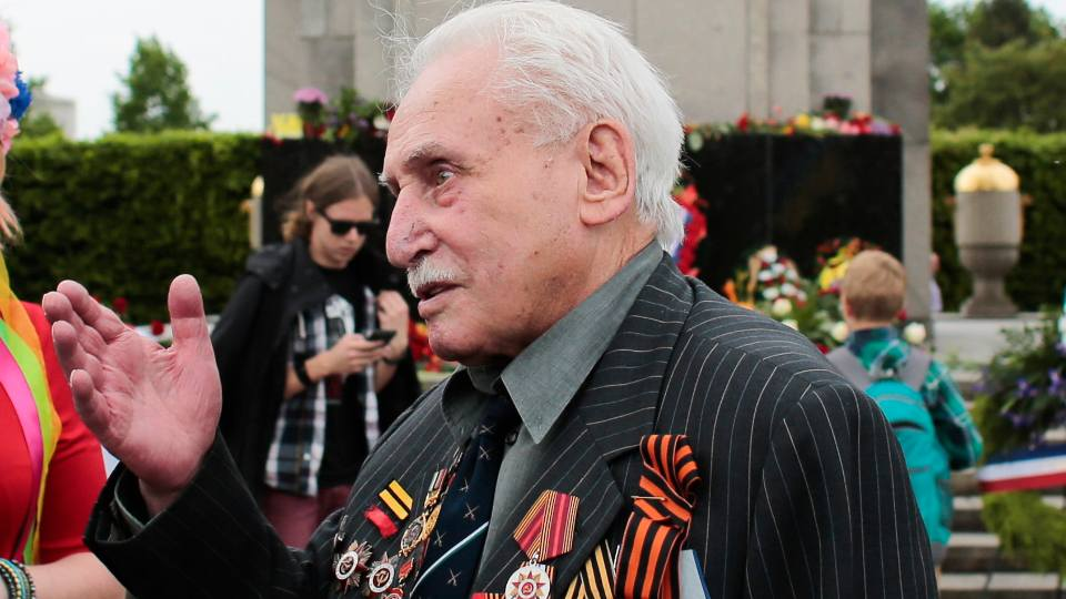 In this Friday, May 8, 2015 file photo, Soviet war veteran David Dushman, 92, center, speaks to people holding Ukrainian flags as he attends a wreath laying ceremony at the Russian War Memorial in the Tiergarten district of Berlin, Germany. Dushman, the last surviving Allied soldier involved in the liberation of Auschwitz, has died. The Jewish Community of Munich and Upper Bavaria said Sunday, June 6, 2021 that Dushman had died a day earlier in a Munich hospital at the age of 98. As young Red Army soldier, Dushman flattened the forbidding fence around the notorious Nazi death camp with his tank on Jan. 27, 1945.
