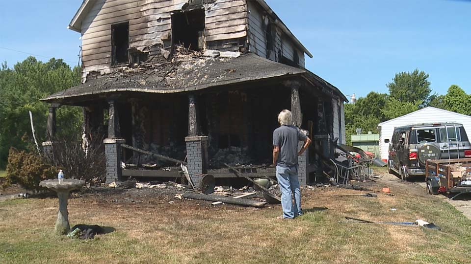 Victor Barich looks up at the remnants of his East Side home following a fire Wednesday afternoon