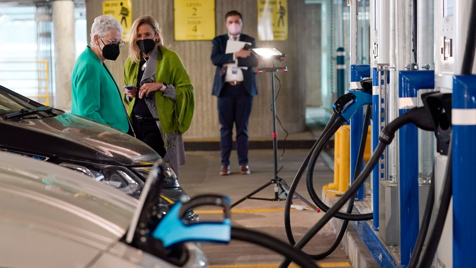 In this Thursday, April 22, 2021 file photo, White House climate adviser Gina McCarthy, left, talks with EVgo Chief Executive Officer Cathy Zoi, before the start of an event near an EVgo electric car charging station at Union Station in Washington.