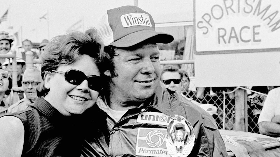 Jack Ingram gives his wife, Aline, a big hug after accepting the trophy from his victory in the Permatex 300 auto race at Daytona International Speedway in Daytona Beach, Fla. Ingram, a hard-hosed, hot-tempered racer who won five NASCAR championships and more than 300 races, has died, the NASCAR Hall of Fame said Friday, June 25, 2021