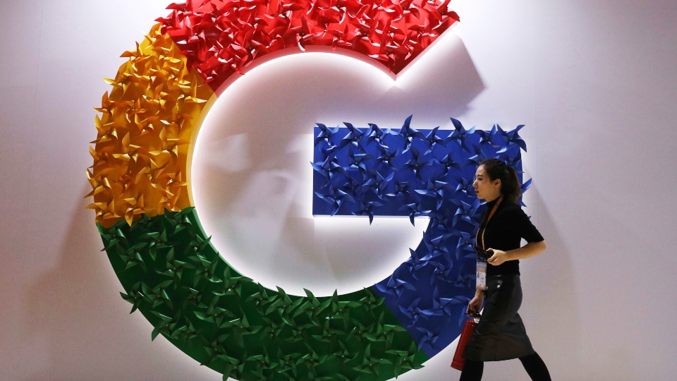 In this Monday, Nov. 5, 2018 file photo, a woman walks past the logo for Google at the China International Import Expo in Shanghai.