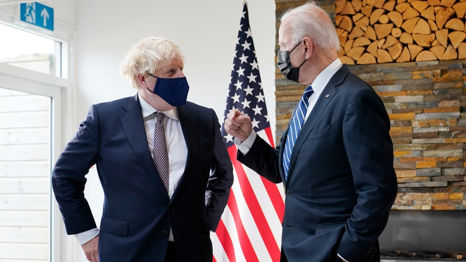 President Joe Biden and British Prime Minister Boris Johnson talk as they look over copies of the Atlantic Charter, during a bilateral meeting ahead of the G-7 summit, Thursday, June 10, 2021, in Carbis Bay, England.