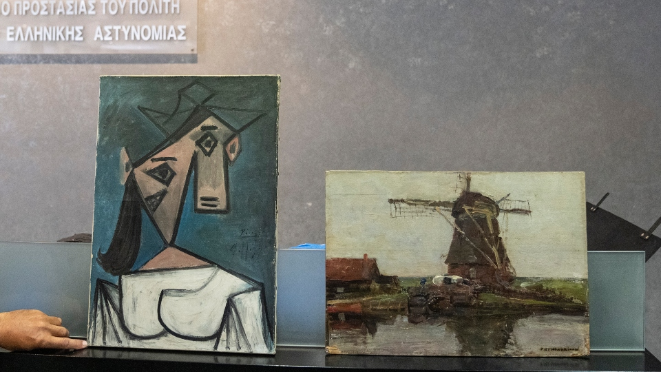 A cubist female bust by the Spanish painter Picasso, left, and a 1905 representational oil painting of a riverside windmill by the Dutch painter Mondrian are displayed by police officers, in Athens during a press conference, on Tuesday, June 29, 2021.