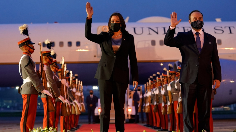 Vice President Kamala Harris and Guatemala's Minister of Foreign Affairs Pedro Brolo wave at her arrival cermony in Guatemala City, Sunday, June 6, 2021, at Guatemalan Air Force Central Command.