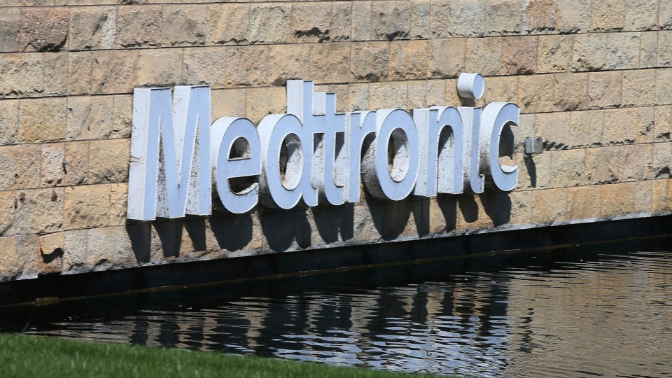In this Aug. 29, 2019 file photo, the Medronic logo is reflected in a lake at the company's offices in Fridley, Minn.