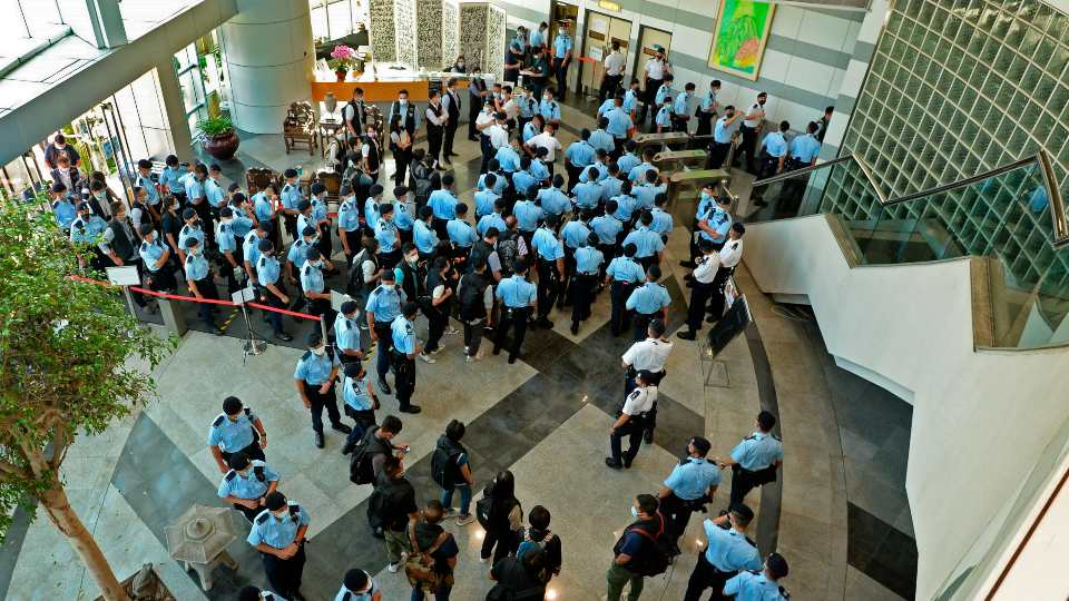 Police officers gather at the lobby of headquarters of Apple Daily in Hong Kong Thursday, June 17, 2021. Hong Kong police on Thursday morning arrested the chief editor and four other senior executives of Apple Daily under the national security law on suspicion of collusion with a foreign country to endanger national security, according to local media reports.