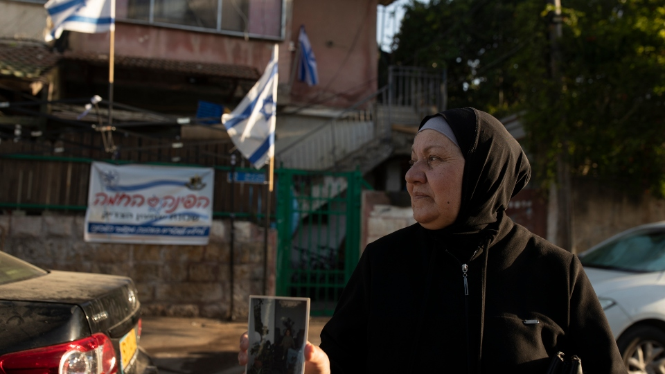 Maryam Ghawi, a Palestinian, holds a family photo taken in the home behind her that is now occupied by Israeli settlers in the Sheikh Jarrah neighborhood of east Jerusalem.