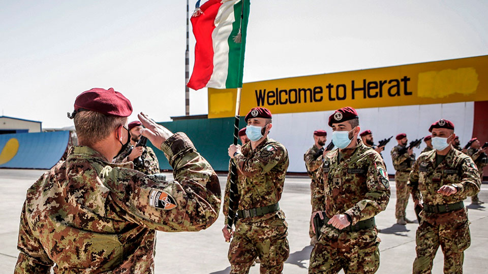 Italian Army soldiers carry the flag of the Folgore Brigade as the last Italian troops withdraw from Afghanistan