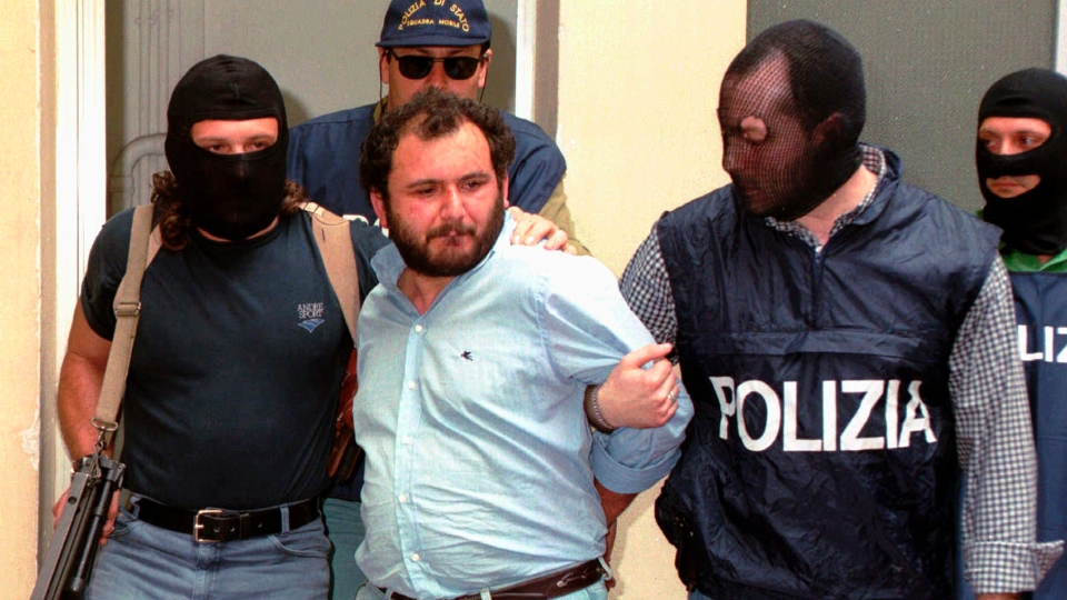 In this file photo taken on May 21, 1996, Giovanni Brusca is escorted by masked policemen outside Police H.Q. in Palermo, Sicily.