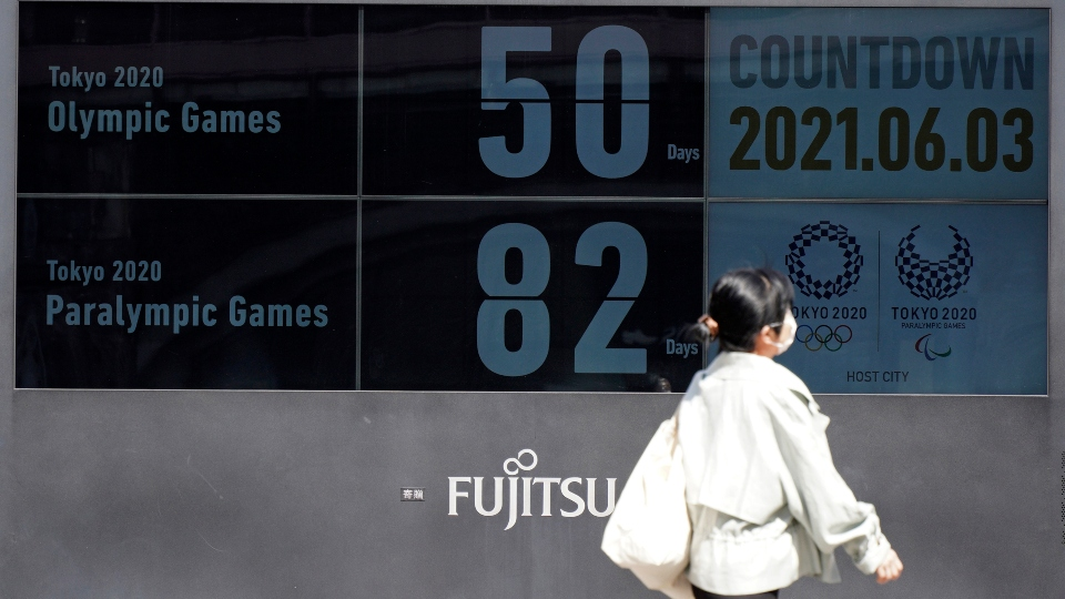 People walk past the countdown clock for the Tokyo 2020 Olympic and Paralympic Games near Shimbashi station in Tokyo, Thursday, June 3, 2021, to mark 50 days before the start of the Summer Games.