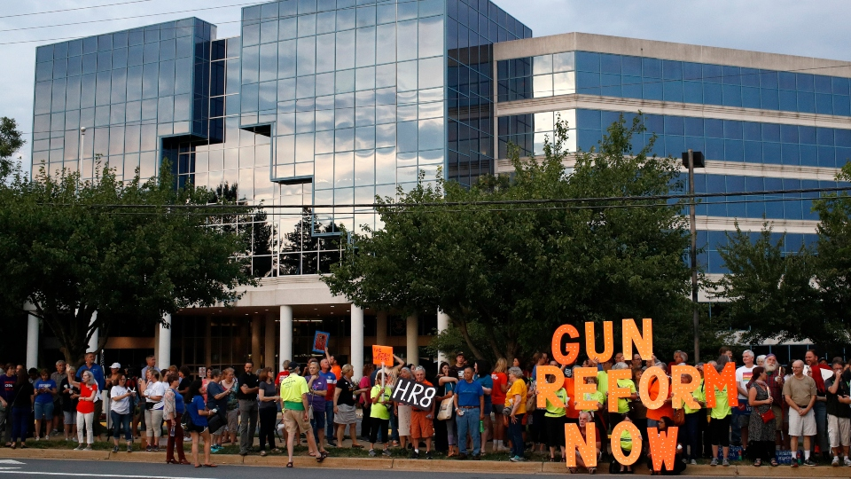 In this Aug. 5, 2019, file photo, people gather at a vigil for recent victims of gun violence outside the National Rifle Association's headquarters building in Fairfax, Va.