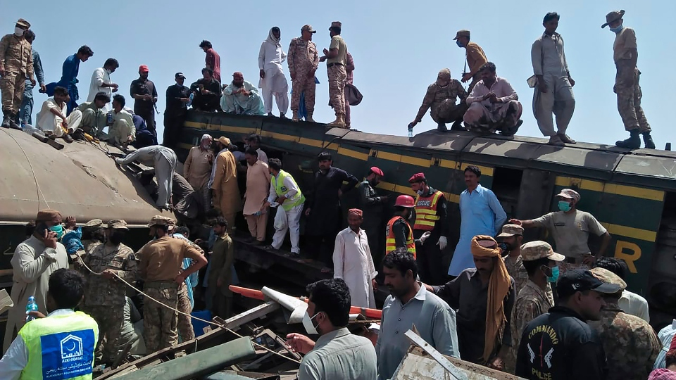 Soldiers and volunteers work at the site of a train collision in Ghotki district in southern Pakistan, Monday, June 7, 2021.