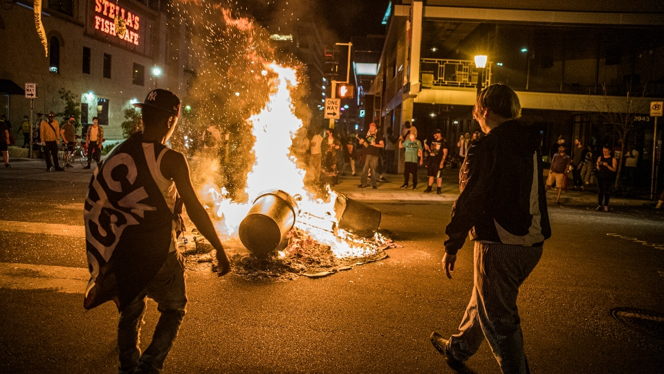 Protesters set a dumpster on fire after a shooting on Thursday, June 3, 2021 in Minneapolis.