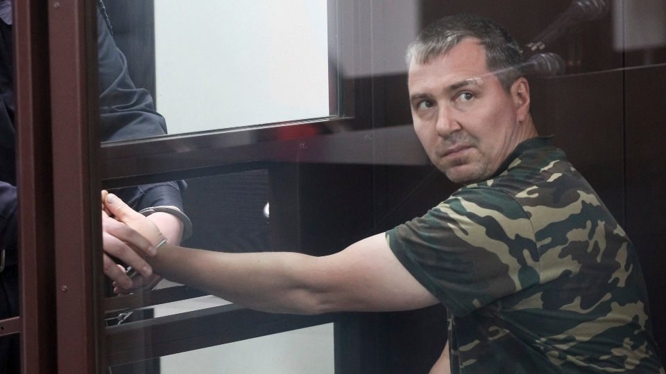 Alexander Popov, a man who was arrested on suspicion of murder sits behind the glass in a courtroom in the city of Gorodets, 60 km.