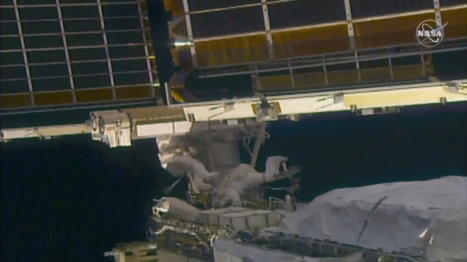 In this image taken from NASA video, NASA astronaut Shane Kimbrough, left, and French astronaut Thomas Pesquet work on the solar array outside the International Space Station, Sunday, June 20 2021.