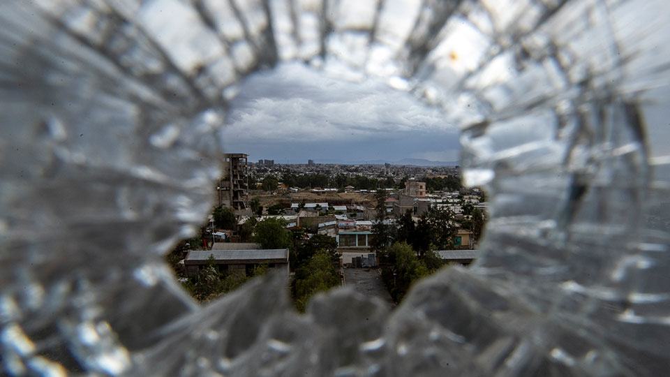 The city of Mekele is seen through a bullet hole in a stairway window of the Ayder Referral Hospital, in the Tigray region of northern Ethiopia