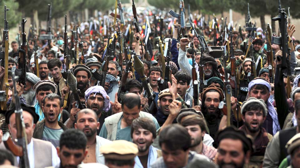 In this June 23, 2021, photo, Afghan militiamen join Afghan defense and security forces during a gathering in Kabul, Afghanistan. U.S. officials tell The Associated Press that about 650 U.S. troops are expected to be kept in Afghanistan to provide security for the American diplomatic presence after the Pentagon completes its military withdrawal, which is set to be largely done in the next two weeks. (AP Photo/Rahmat Gul)