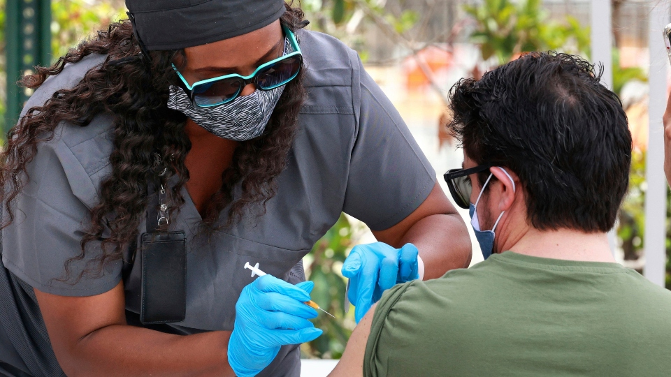 In this June 17, 2021, file photo, an Orange County resident receives the COVID-19 vaccine at the Florida Division of Emergency Management mobile vaccination site at Camping World Stadium in Orlando, Fla.